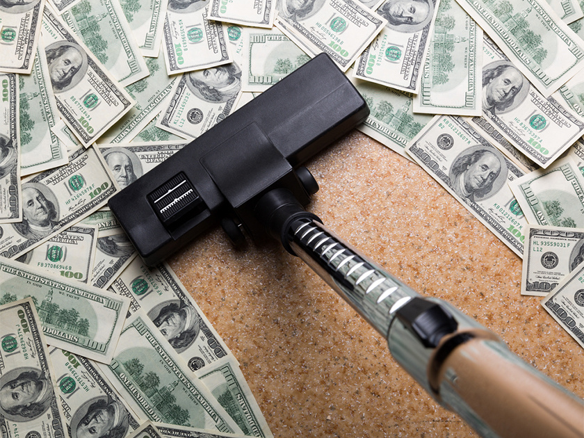 Money on the floor vacuuming with vacuum cleaner